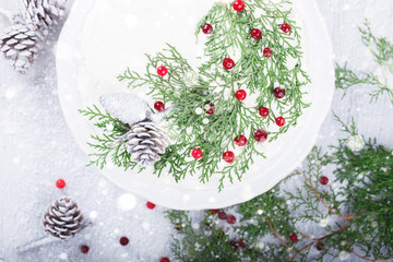 Cake with white cream,garnished with sprigs of spruce ,pine cones,cranberries.Christmas pastries.Holiday Card.Drawn Snowfall. selective focus.