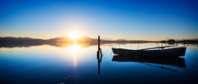 Perfectly Specular Reflection On The Calm Pond At Dawn With A Fisherman Boat - Clear Blue Sky With Sun Warm Light