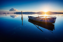 Perfectly Specular Reflection On The Calm Pond At Dawn With A Fisherman Boat