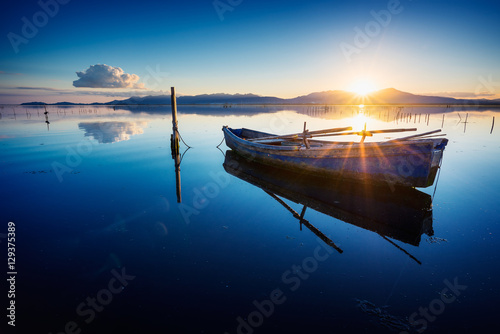 Fototapeta Perfectly specular reflection on the calm pond at dawn with a fisherman boat
