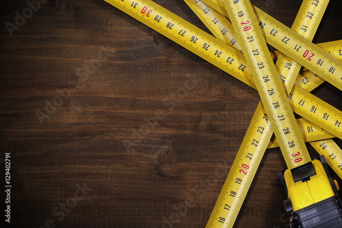 Fényképezés  Tape Measures on Brown Wooden Background