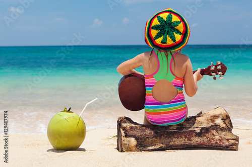 Little happy baby in rastaman hat have fun, play reggae music on Hawaiian guitar, enjoy relaxing on ocean beach Wallpaper Mural