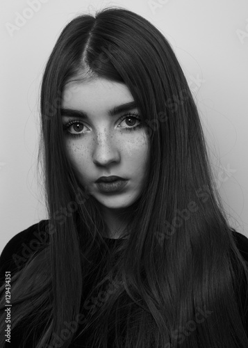 Dramatic black and white portrait of a beautiful lonely girl with freckles isolated on a white