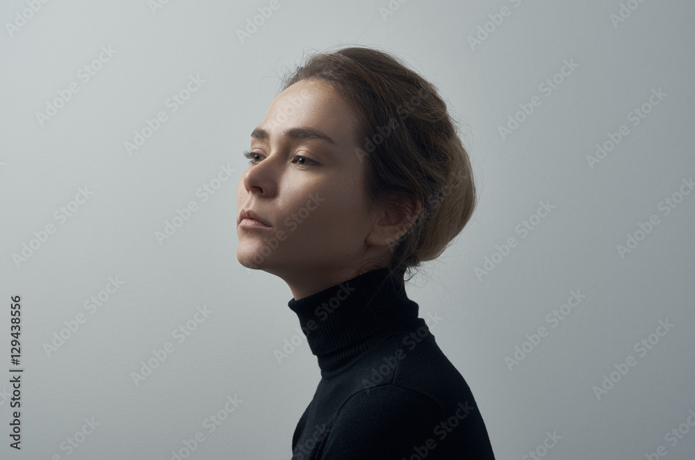 Fototapeta Dramatic portrait of a young beautiful girl with freckles in a black turtleneck on white background in studio