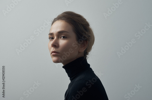 Dramatic portrait of a young beautiful girl with freckles in a black turtleneck Wallpaper Mural