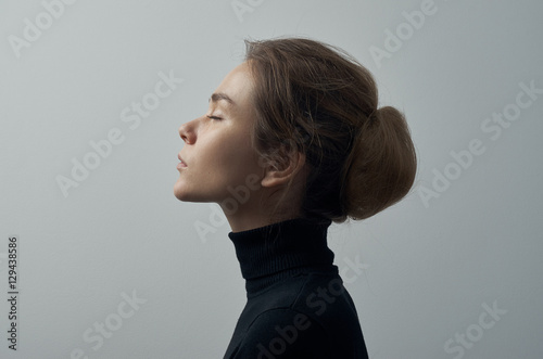 Foto  Dramatic portrait of a young beautiful girl with freckles in a black turtleneck