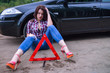 Woman sitting near her broken car and warning triangle