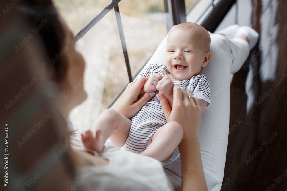 Fototapety, obrazy: A beautiful woman, a young mother, brunette with long hair, dressed in a white shirt and white pants on his knees to her newborn child, dressed in a striped t-shirt sitting near the window