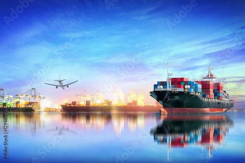 Fotografia, Obraz  Logistics and transportation of international container cargo ship and cargo plane with ports crane bridge in harbor at sunset sky for logistics import export background and transport industry