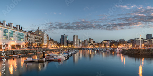City on the water Yatchs and pier in leisure port on maritime fishing district of Gijon, Spain, Europe. Beautiful reflection on calm sea water of boats, buildings, sky at dusk at touristic cultural travel destination.