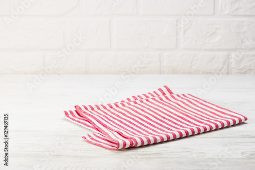 Fototapeta Red napkin isolated on white wooden table. Copy space. Brick wall background. Front view. obraz
