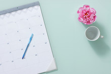 Calendar With Coffee Cup And Pink Carnation Flower On Light Turquoise Background