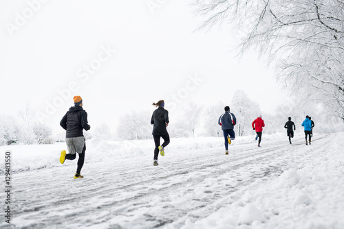 Papiers peints Glisse hiver group young people running together snowy trail in winter Park. rear view