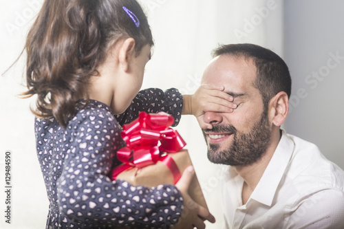 Girl hiding gift while covering happy father eyes