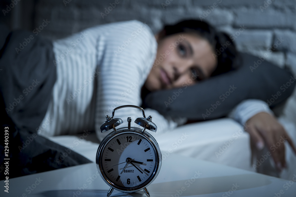 Fototapeta hispanic woman at home bedroom lying in bed late at night trying to sleep suffering insomnia