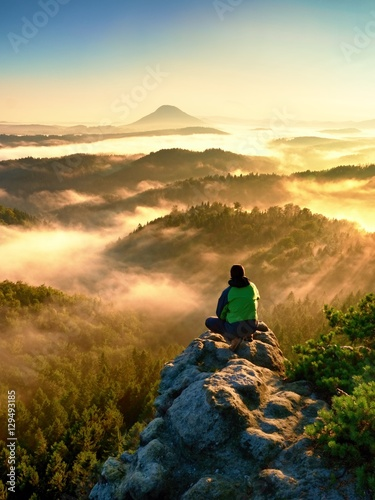 Man tourist sit on exposed rock. View point with heather and branches Wall mural