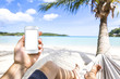 Using smartphone on a tropical paradise beach sitting in hammock