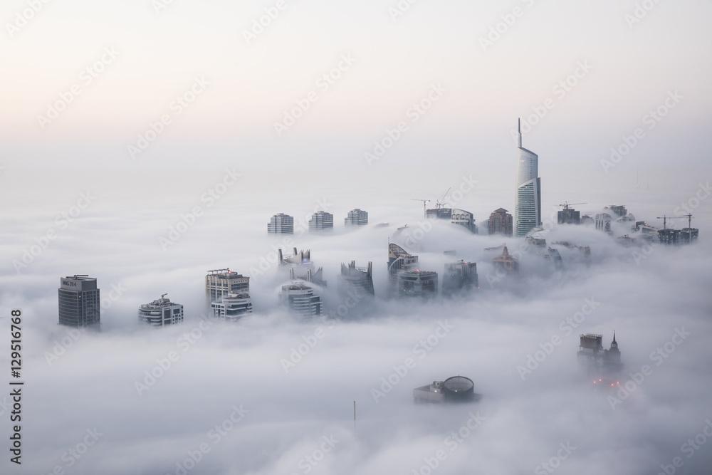 Fototapety, obrazy: Rare early morning winter fog above the Dubai Marina skyline and skyscrapers ahead of sunrise in Dubai, United Arab Emirates.