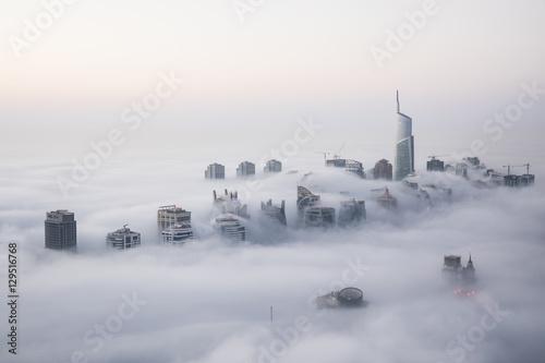 Obraz Rare early morning winter fog above the Dubai Marina skyline and skyscrapers ahead of sunrise in Dubai, United Arab Emirates. - fototapety do salonu