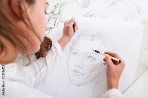 Artist drawing pencil portrait close-up. Woman painter creating picture of woman on big whatman. Art, talent, craft, hobby, occupation concept