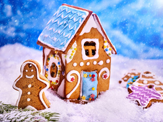 Christmas gingerbread man close up outside of gingerbread house. Christmas cookies in the background in the snow. Winter background.