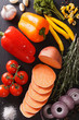 Background of raw vegetables: sweet potatoes, peppers, tomatoes, onions, garlic, rosemary and spices. vertical top view