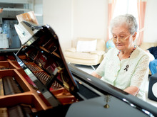 Senior Woman Pianist Play Piano With Happiness At Home