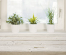 Wooden Table On Blurred Winter Window With Plant Pots Background