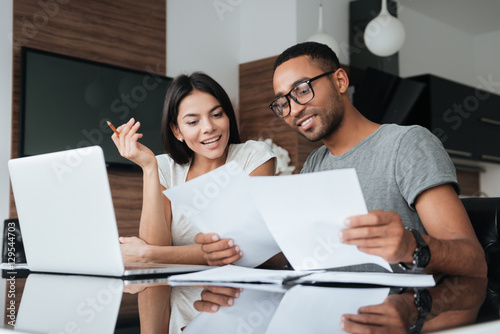 Photo  Cheerful loving young couple using laptop and analyzing finances