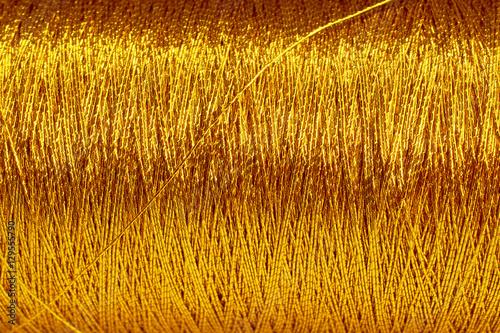 Fotografiet  the spool of gold thread closeup horizontal