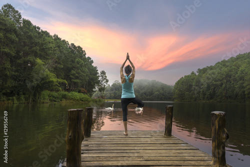 Young woman is practicing yoga at lake