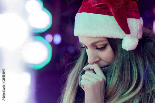 фотография  Sad woman by the christmas tree contemplating. Lonely Christmas
