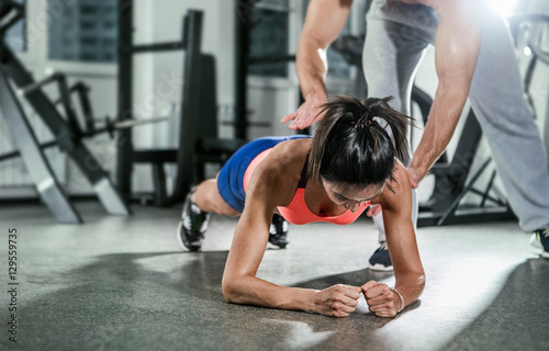 Fotografija  Trainer assisting a muscular woman on a plank position