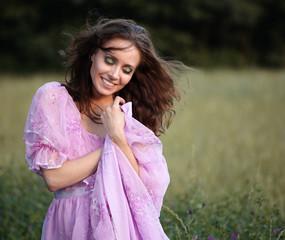 Portret uśmiechniętej kobiety w liliowej sukience