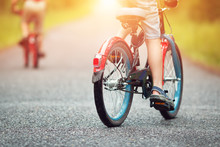 Children On A Bicycle At Asphalt Road In Early Morning