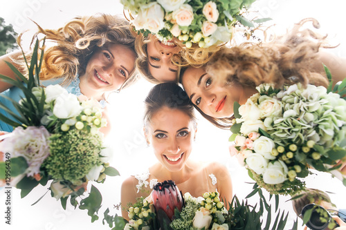 Fotografia Look from below at happy bride and bridesmaids holding wedding b