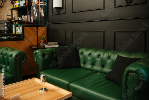 Microphone on table against restaurant background with sofa