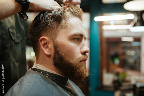Spoed Foto op Canvas Muziekwinkel Young man getting haircut by hairdresser with scissors