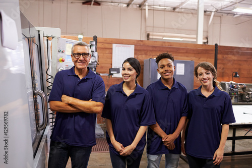 Portrait Of Engineer Training Apprentices On CNC Machine