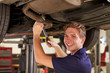 Portrait Of Auto Mechanic Working Underneath Car In Garage