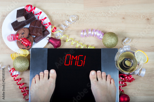 Obraz na plátně  Digital scales with female feet on them and signomg! surrounded by christmas decorations, sweets and alchohol