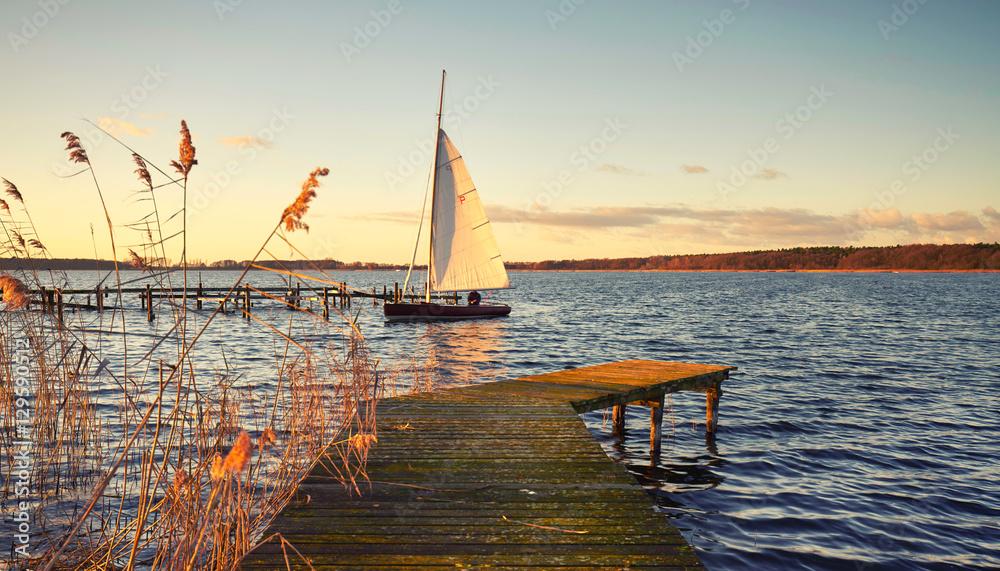 Segelboot am Steg im Abendlicht
