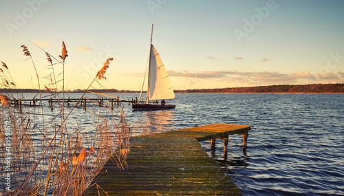 Fotografia  Segelboot am Steg im Abendlicht