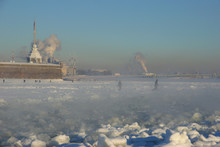 Cold Winter Day In The City Of St. Petersburg. View Of Naryshkin Bastion, Peter And Paul Fortress Through The Steam Rising Over Ice Channel To Navigate The Frozen Neva River. People Walk On The Ice.