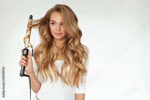 Plakat Kręcone włosy. Piękna kobieta Curling długie falowane włosy z żelaza