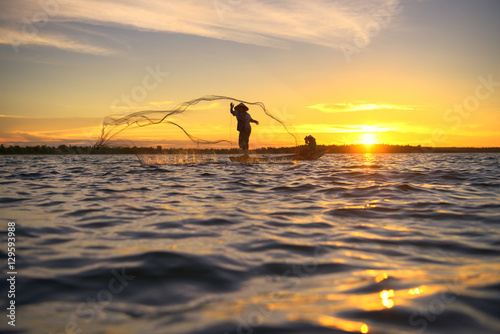 Poster Marron chocolat Silhouette of traditional fisherman throwing net fishing lake at sunrise time