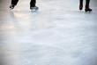 Schlittschuhe laufen / Die Nahaufnahme der Schlittschuhe von Schlittschuhfahrern auf einer Eisfläche.