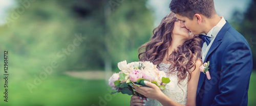 Foto Beautiful young bride and groom kissing in park