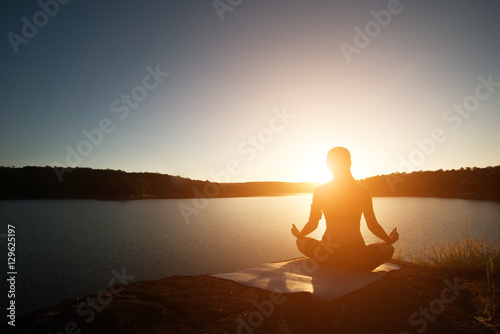 Staande foto School de yoga Silhouette of healthy woman is practicing yoga at mountain lake