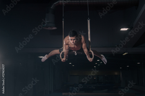 Spoed Fotobehang Gymnastiek young man gymnast, gymnastics rings in air